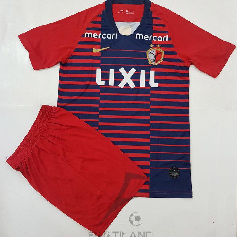 پیراهن شورت اول کاشیما 2020 با زمینه قرمز و خط راه راه سورمه ای یقه پیراهن هفت بصورت تیشرت آستین کوتاه